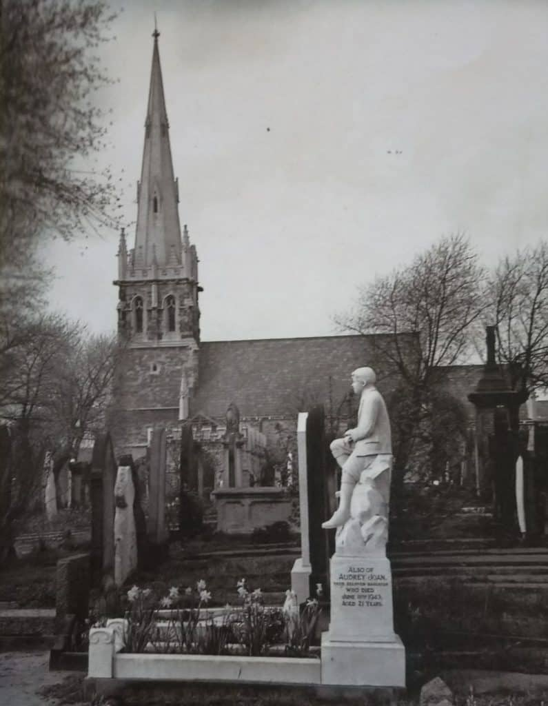 Black and white photo of Warstone Lane cemetery with white marble statue of boy in foreground and chapel in background.